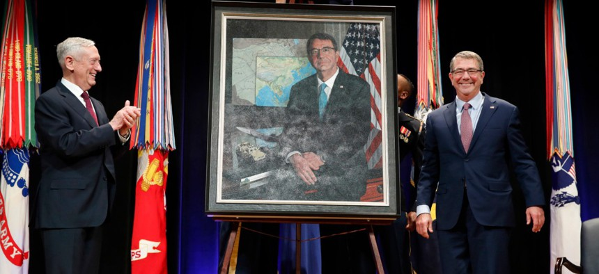 Then Defense Secretary James Mattis, left, applauds former Defense Secretary Ash Carter, right, during the portrait unveiling ceremony for the former secretary at the Pentagon in February 2018.