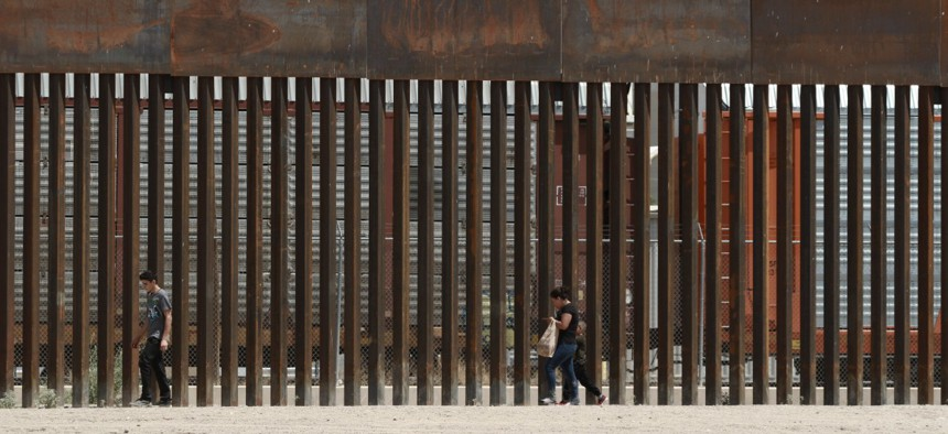 Three migrants who had managed to evade the Mexican National Guard and cross the Rio Grande onto U.S. territory walk along a border wall set back from the geographical border, in El Paso, Texas, as seen from Ciudad Juarez, Mexico, in July.