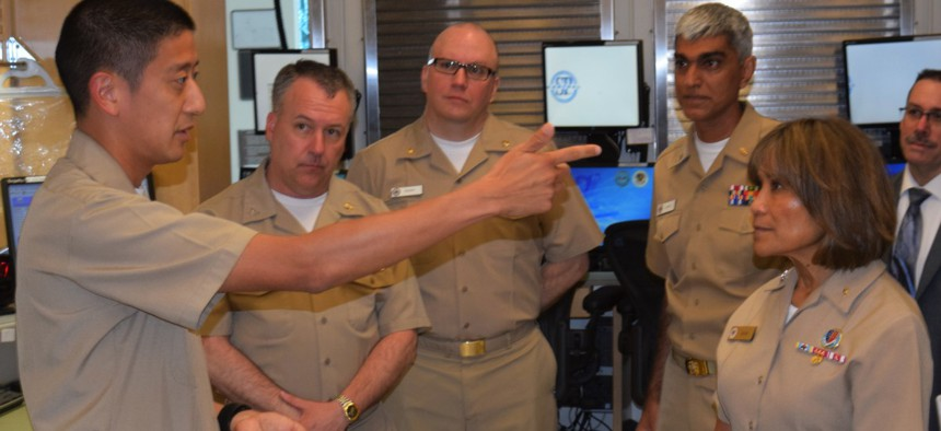 Navy Vice Adm. Raquel Bono receives candid feedback on deploying MHS GENESIS at Naval Hospital Bremerton from the command's pharmacy department head, Lt. Cmdr. Dean Kang, in June 2018.