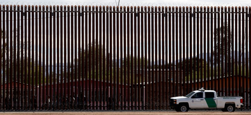 A Customs and Border Protection vehicle sits near the wall along a new section of the border wall with Mexico in Calexico, Calif.