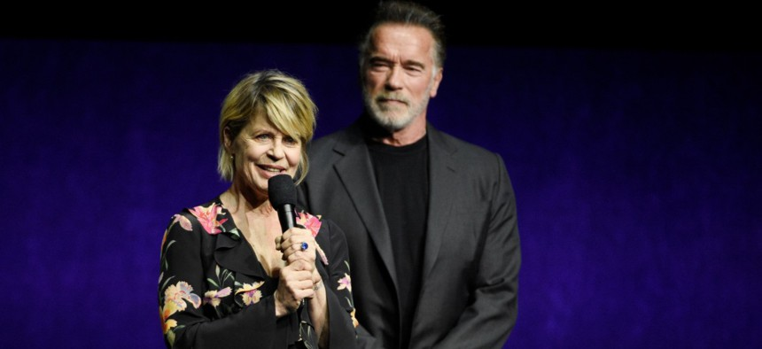 """Linda Hamilton discusses """"Terminator: Dark Fate"""" onstage as fellow cast member Arnold Schwarzenegger looks on during the Paramount Pictures presentation at CinemaCon 2019 in April."""
