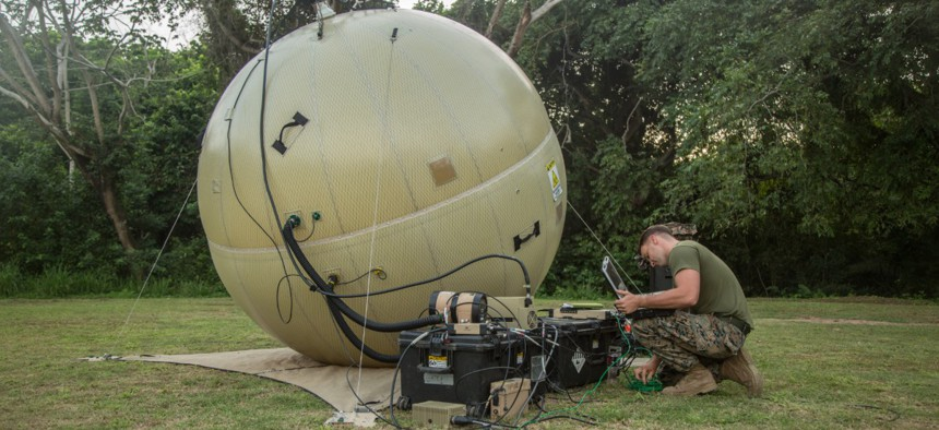 A Marine finalizes adjustments on a ground antenna transmit and receive communications system during the setup of a command operations center in Base de Entrenamiento de Infanteria de Marina, Coveñas, Colombia, in September.