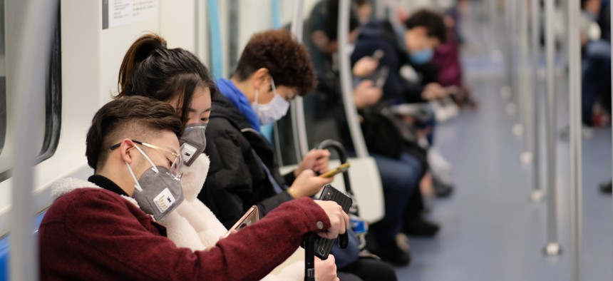 Subway commuters in Shanghai wear face masks during the coronavirus outbreak.