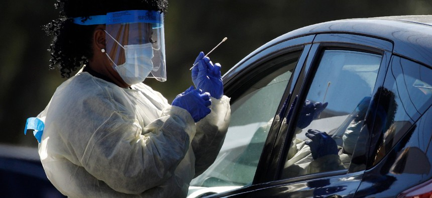 A health care worker with the UNLV School of Medicine tests a patient for the coronavirus at a drive-thru testing site March 24 in Las Vegas.
