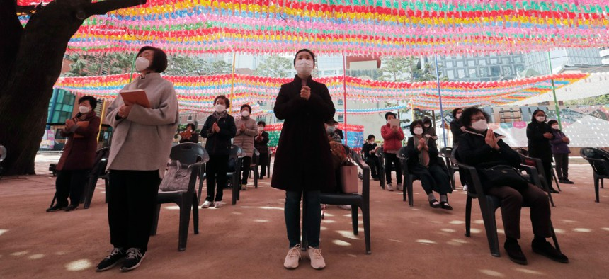 People wearing face masks pray while maintaining social distancing during a service at the Chogyesa temple in South Korea April 24.