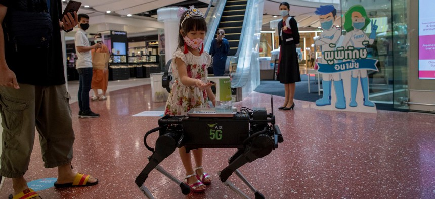 A child disinfects her hands from a mobile robot that carries a container of sanitization liquid at Central World, an upmarket shopping mall in Bangkok, Thailand, Wednesday, May 27, 2020.