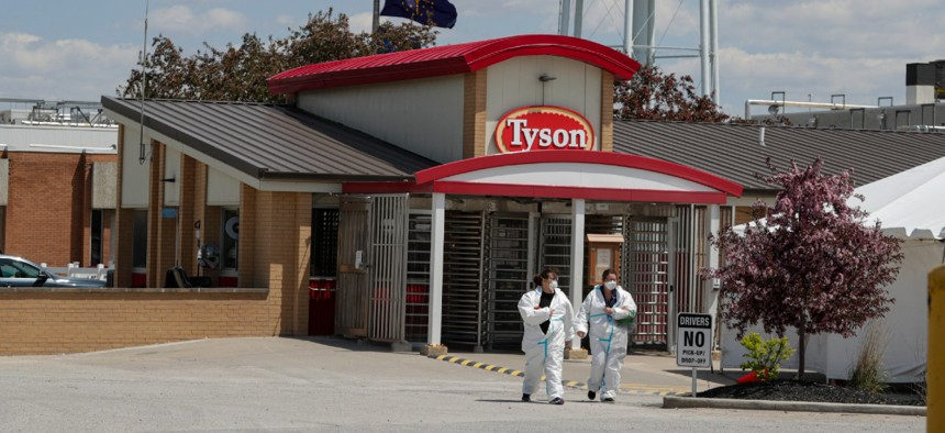 In this May 7, 2020, file photo, workers leave the Tyson Foods pork processing plant in Logansport, Ind.