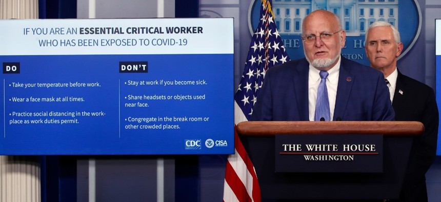 CDC Director Robert Redfield speaks as charts are displayed during a briefing about the coronavirus at a White House briefing April 8 as Vice President Mike Pence listens.