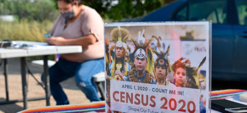 A sign promoting Native American participation in the U.S. census is displayed as Selena Rides Horse enters information into her phone on behalf of a member of the Crow Indian Tribe in Lodge Grass, Mont. on Wednesday, Aug. 26, 2020.