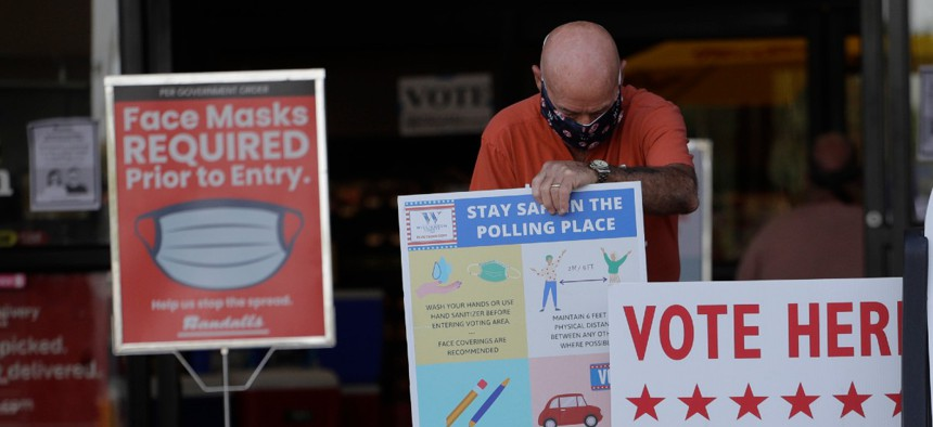 An election worker wearing a mask for protection against COVID-19 adjust signs for an early polling site located at a grocery store, Thursday, July 9, 2020, in Austin, Texas.