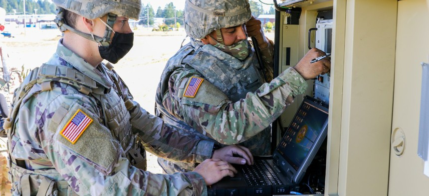 A U.S. Army signal specialist and an information technology Specialist prepare their equipment as part of the Spartan Week Convoy Operations on Sept. 29 at Joint Base Lewis-McChord, Wash.