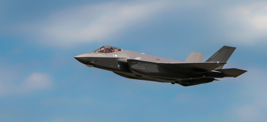 """Military F35 fighter jet flying. Blue sky with clouds. Lockheed Martin F-35B """"Lightning"""" II"""