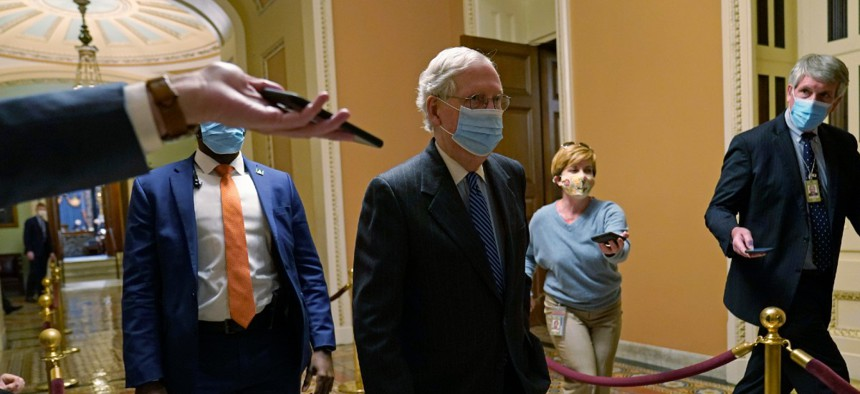 Senate Majority Leader Mitch McConnell of Ky., walks past reporters on Capitol Hill Dec. 15.