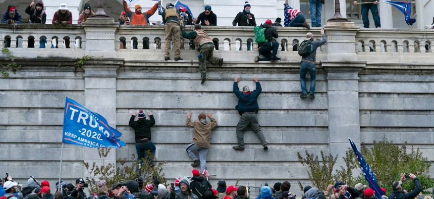 Supporters of President Donald Trump climb the west wall of the the U.S. Capitol in Washington Jan. 6.