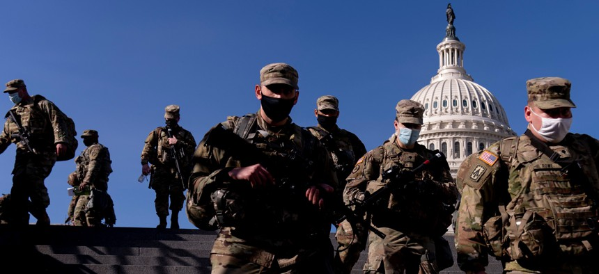 Members of the National Guard walk past the Dome of the Capitol Building on Capitol Hill in Washington Jan. 14.