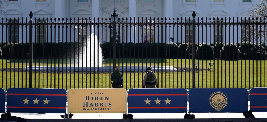 A security team patrols in front of the White House as preparations continue ahead of President-elect Joe Biden's inauguration ceremony, Tuesday, Jan. 19, 2021, in Washington.