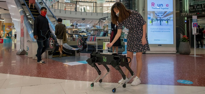 A woman disinfects her hands from a mobile robot that carries a container of sanitization liquid at Central World, an upmarket shopping mall in Bangkok, Thailand in May 2020.