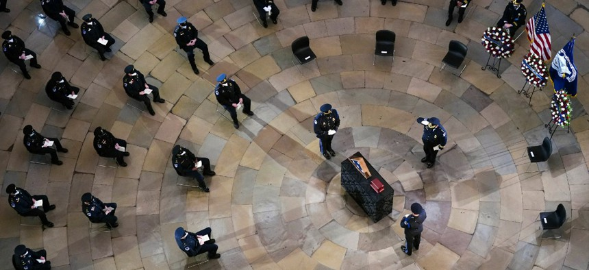 Mourners pay their respects during a ceremony memorializing U.S. Capitol Police officer Brian Sicknick, as an urn with his cremated remains lies in honor on a black-draped table at the center of the Capitol Rotunda Feb. 3.