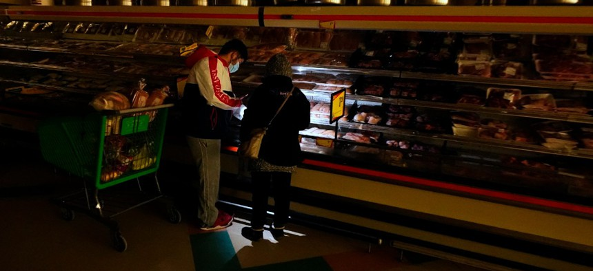 Customers use the light from a cell phone to look in the meat section of a grocery store Tuesday, Feb. 16, 2021, in Dallas. Even though the store lost power, it was open for cash only sales.