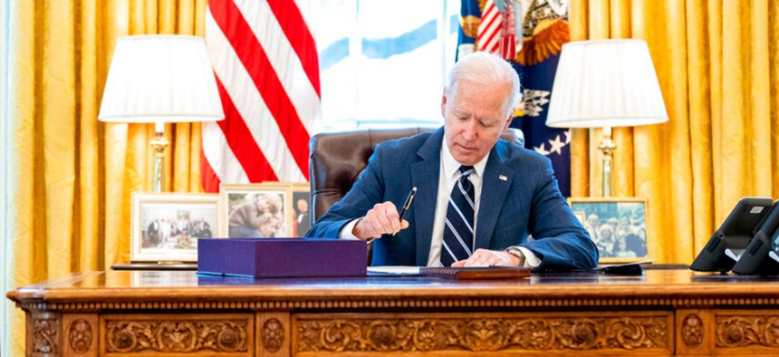 President Joe Biden signs the American Rescue Plan, a coronavirus relief package, in the Oval Office of the White House March 11.