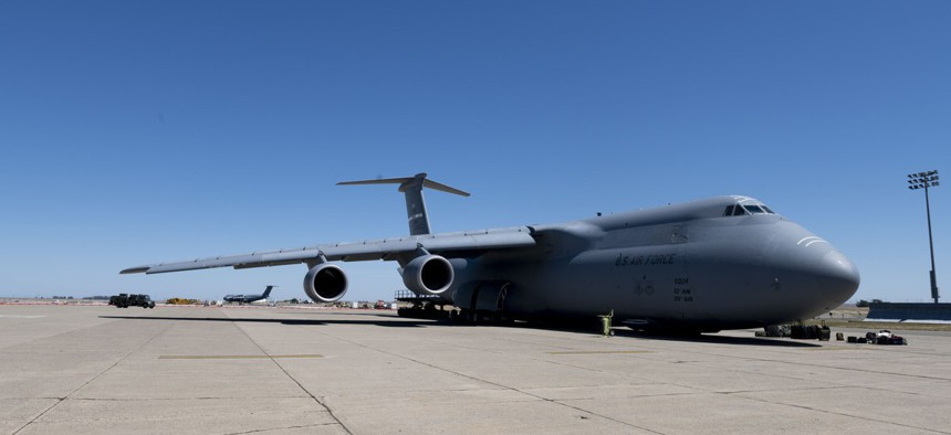 Airmen from the 60th Aerial Port Squadron prepare to load COVID-19 supplies onto a C-5M Super Galaxy as it sits on the flight line at Travis Air Force Base, California, April 28.