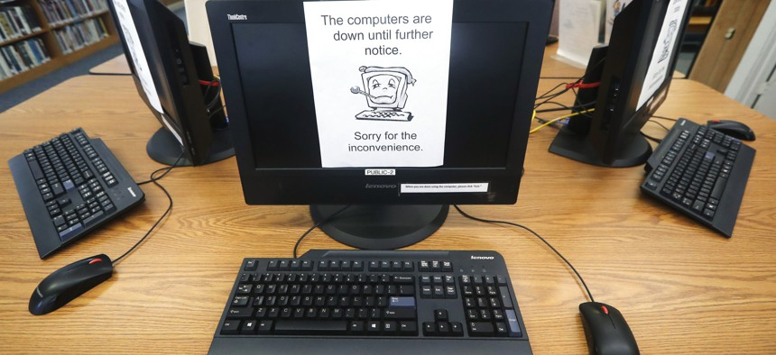 In this Aug. 22, 2019 photo, signs on a bank of computers tell visitors that the machines are not working at the public library in Wilmer, Texas.