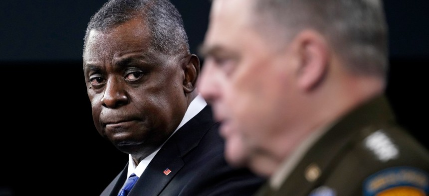 Defense Secretary Lloyd Austin, left, listens as Chairman of the Joint Chiefs of Staff Gen. Mark Milley, right, speaks during a briefing at the Pentagon in Washington, Thursday, May 6, 2021.