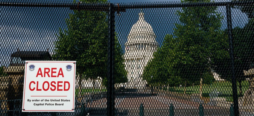 The U.S. Capitol is seen under dark skies in Washington, Tuesday, June 8, 2021, as barriers remain six months after the Jan. 6 attack.