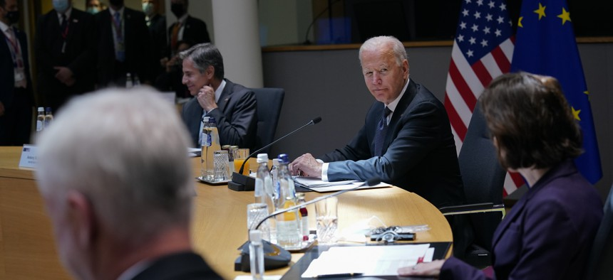 President Joe Biden attends the United States-European Union Summit with Secretary of State Antony Blinken, back left, and Commerce Secretary Gina Raimondo, right, at the European Council in Brussels, Tuesday, June 15, 2021.