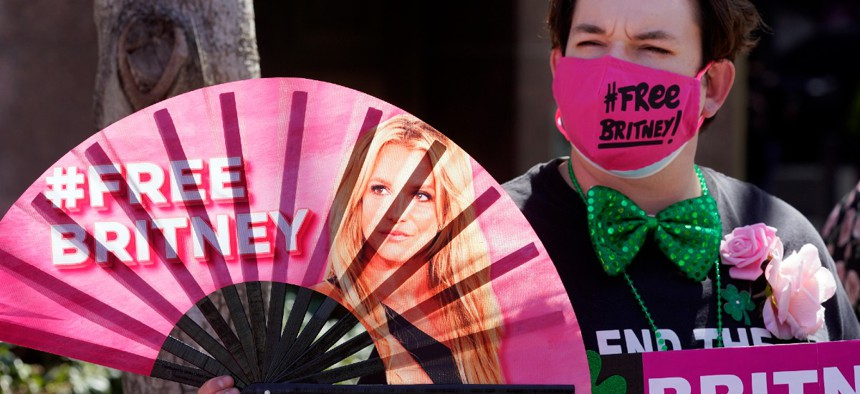 Britney Spears supporter Dustin Strand of Phoenix holds a hand fan outside a court hearing concerning the pop singer's conservatorship at the Stanley Mosk Courthouse, Wednesday, March 17, 2021, in Los Angeles.