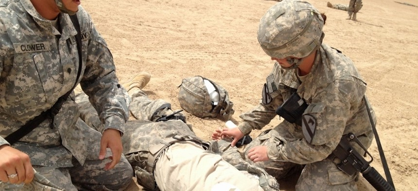 Spc. Melinda Clower (left) and Spc. Lacey Duffy (right), soldiers assigned to Company C, 115h Brigade Support Battalion, 1st Brigade Combat Team, 1st Cavalry Division, evaluate and treat Spc. Scott Ehrgott (center) during a company field training exercise, April 5.