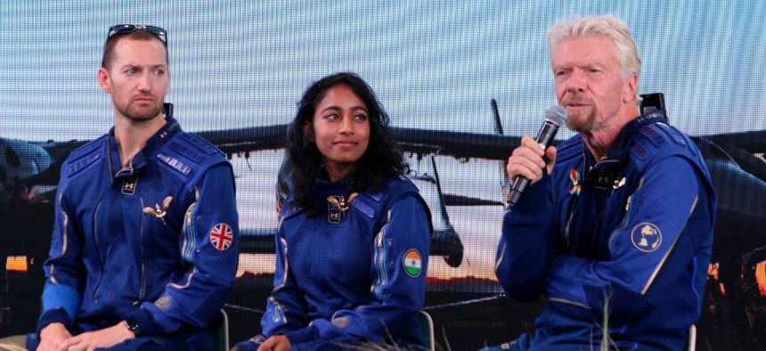 Richard Branson, right, answers questions while crewmates Sirisha Bandla and Colin Bennett listen during a news conference at Spaceport America near Truth or Consequences, N.M., on Sunday, July 11, 2021.