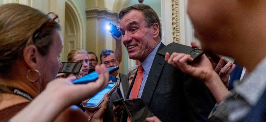 Sen. Mark Warner, D-Va., speaks to reporters after President Joe Biden met with Senate Democrats at the Capitol in Washington July 14.