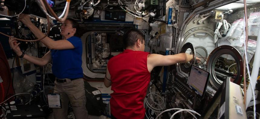 Astronauts Megan McArthur and Akihiko Hoshide work on science maintenance activities inside the International Space Station's U.S. Destiny laboratory module.