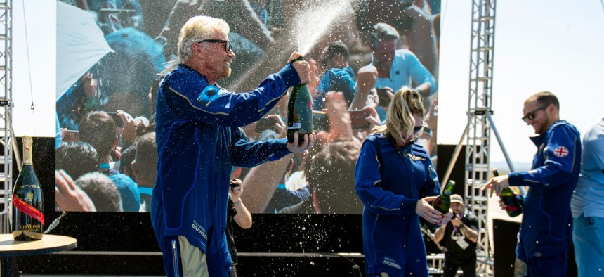 Virgin Galactic founder Richard Branson, left, sprays champagne to crew members while celebrating their flight to space from Spaceport America near Truth or Consequences, N.M., July 11.