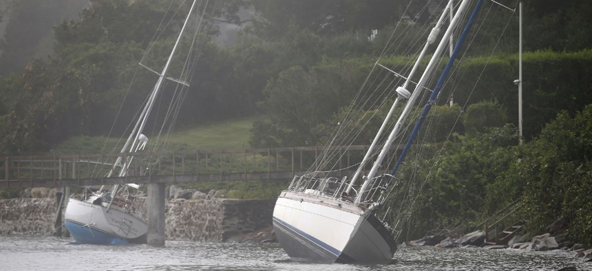 Two sailboats that came loose from their moorings and ran aground during Tropical Storm Henri still sit on the rocks in Jamestown, R.I., Monday.