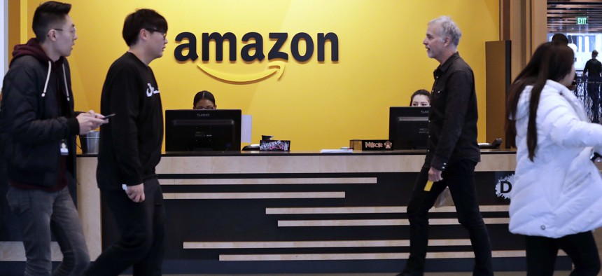 In this Nov. 13, 2018, file photo, employees walk through a lobby at Amazon's headquarters in Seattle.