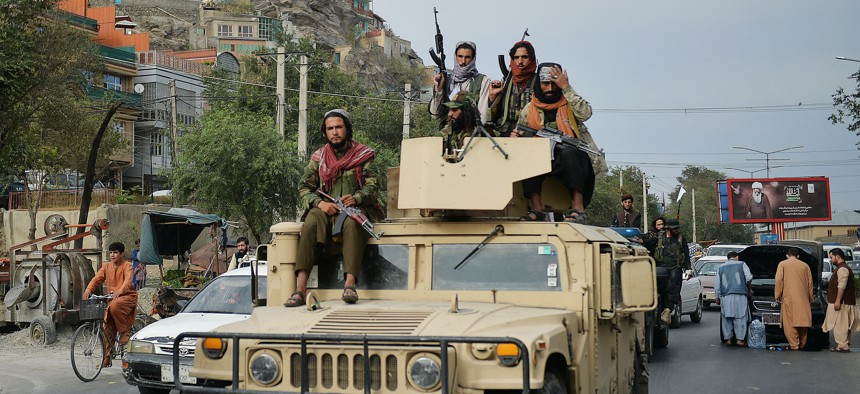 Taliban fighters atop a Humvee vehicle take part in a rally in Kabul on August 31, 2021
