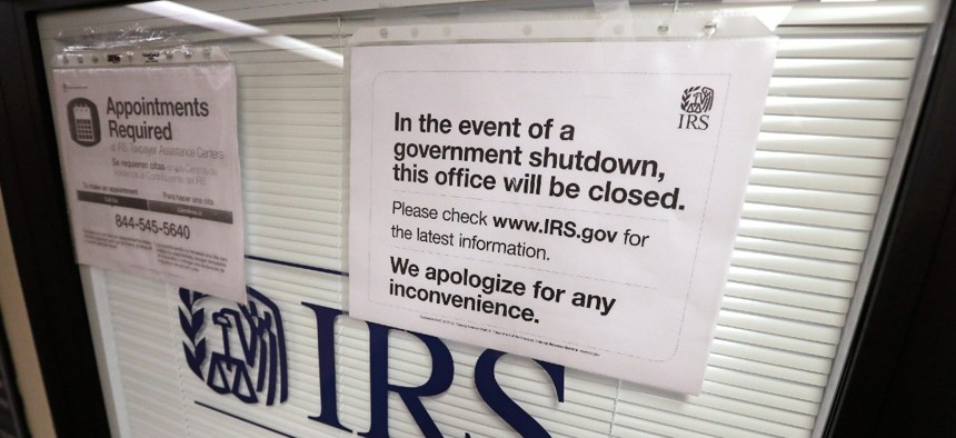 In this Jan. 16, 2019, file photo doors at the Internal Revenue Service (IRS) in the Henry M. Jackson Federal Building are locked and covered with blinds as a sign posted advises that the office will be closed during the partial government shutdown in Seattle.