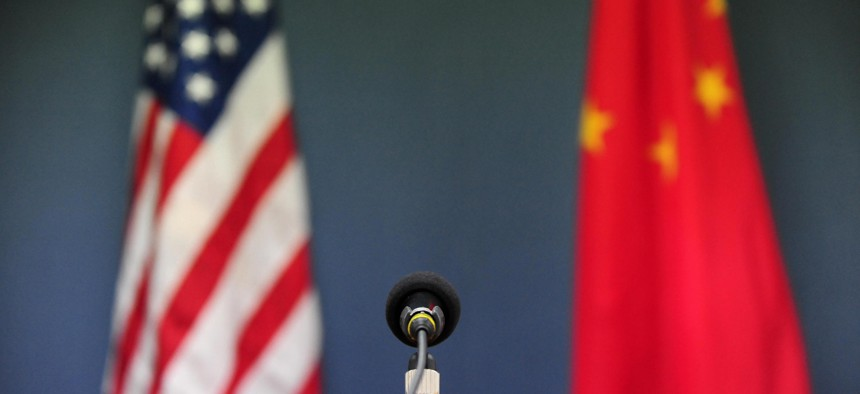 The US and China flags stand behind a microphone.