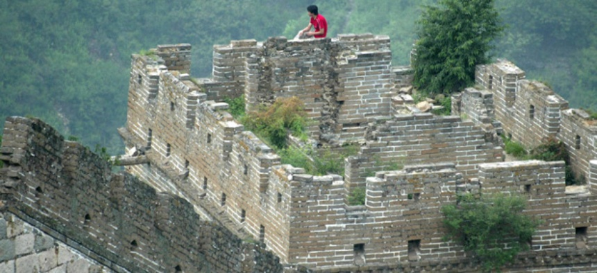 A man rests on a guard tower on the Great Wall of China.