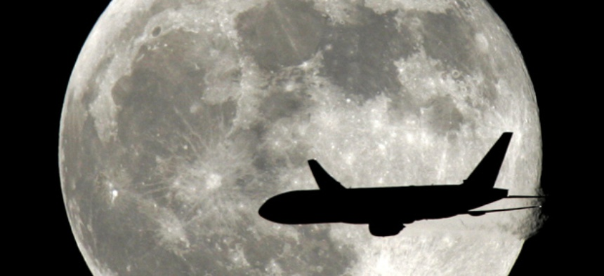 A jet plane passes in front of the full moon.