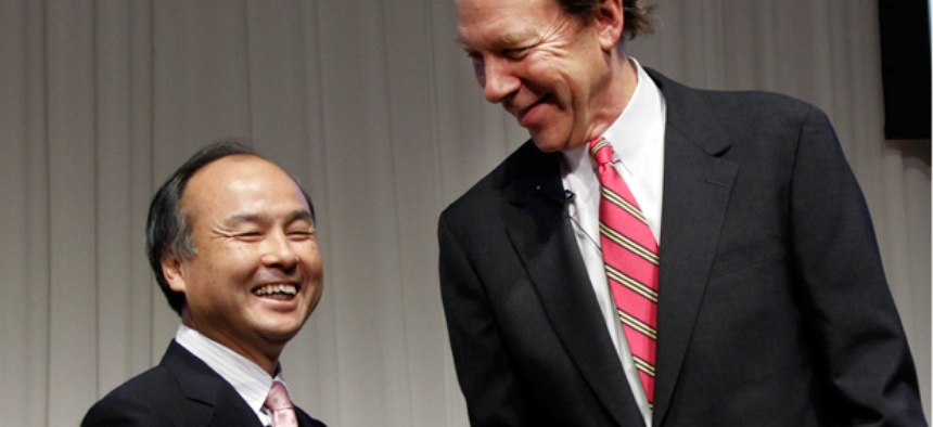 Softbank Corp. President Masayoshi Son, left, and Sprint Nextel Corp. Chief Executive Dan Hesse shake hands.