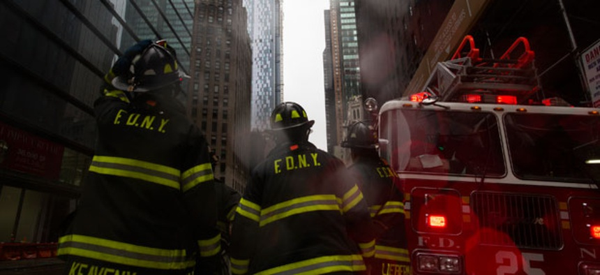 Firefighters respond to a call during the storm in New York Monday.