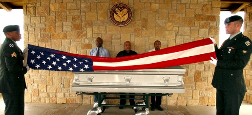 U.S. Army honor guards from Fort Hood, Sgt. Kristopher Tate, left, and Spc. Patrick Debord, right, fold a flag in front of the casket carrying the body of homeless veteran Harold Dean Harris.