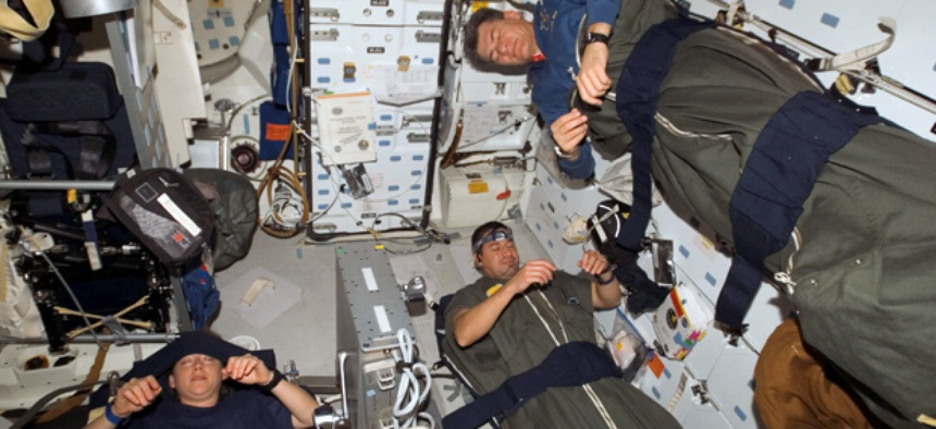 Astronauts Pam Melroy, George Zamka, bottom right,and European Space Agency's Paolo Nespoli, sleep in their sleeping bags, which are secured on the middeck of the Space Shuttle Discovery while docked with the International Space Station.