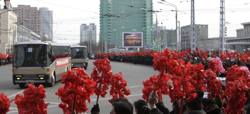 Buses carrying North Korean nuclear scientists was greeted when it arrived in Pyongyang Wednesday.