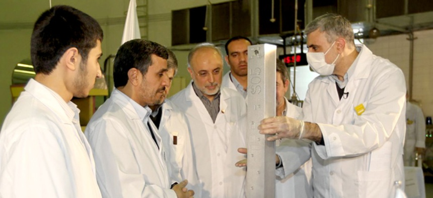 Iranian President Mahmoud Ahmadinejad, second left being escorted by technicians during a tour of Tehran's research reactor center in northern Tehran, Iran.