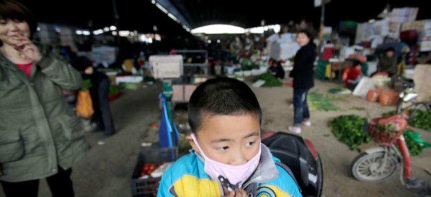 A child wears a mask near the closed poultry section at the Huhuai agricultural market where the H7N9 bird flu was detected by authority in Shanghai, China.