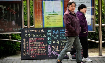 Women walk past a notice on bird flu at a residential area in Minhang district, south of Shanghai, China.